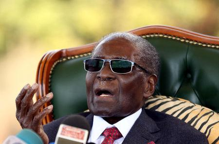 """Zimbabwe's former president Robert Mugabe gestures during a news conference at his private residence nicknamed """"Blue Roof"""" in Harare"""