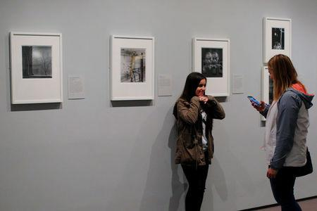 """A visitor poses for a photograph at the exhibit """"Imogen Cunningham: In Focus"""" at the Museum of Fine Arts, Boston, in Boston, Massachusetts, U.S., April 26, 2017. REUTERS/Brian Snyder"""