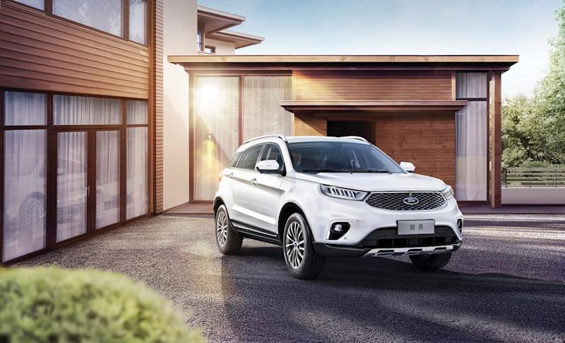 A white 2019 Ford Territory, a compact crossover SUV, in the driveway of an upscale home.