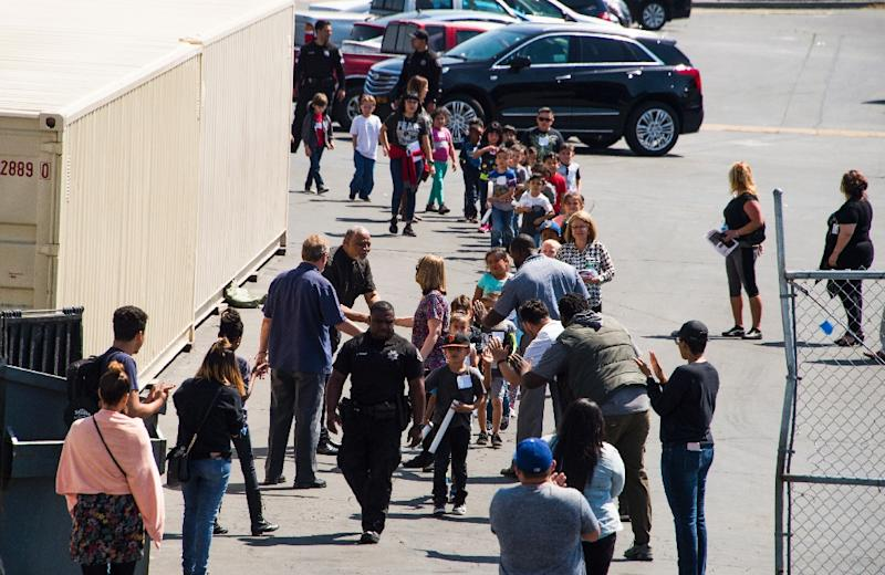 A police officer leads children to be reunited with parents after a gunman entered a classroom and killed one woman and one student, before turning the gun on himself, at North Park Elementary School in San Bernardino, California (AFP Photo/Robyn Beck)