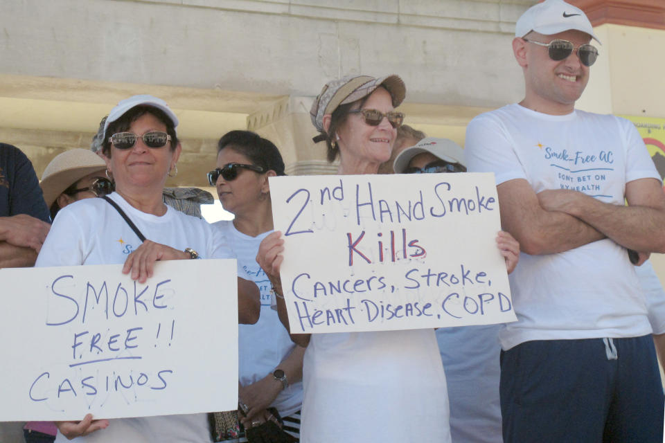 Casino workers hold signs at a rally Wednesday June 30, 2021 in Atlantic City N.J., calling for a permanent ban on smoking in Atlantic City's nine casinos. The coronavirus-inspired temporary ban will end on Sunday July 4. (AP Photo/Wayne Parry)