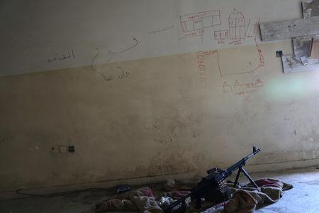 A machine gun is seen on the floor next to a map drawn to show distances in Mosul