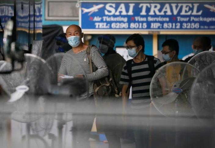Migrant workers board a bus to leave for a government quarantine facility after workers were tested positive for the coronavirus disease (COVID-19) at Westlite Woodlands dormitory in Singapore