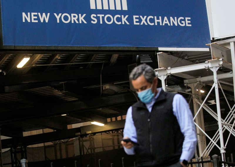 A New York Stock Exchange employee uses his phone on Wall St. outside the NYSE in New York