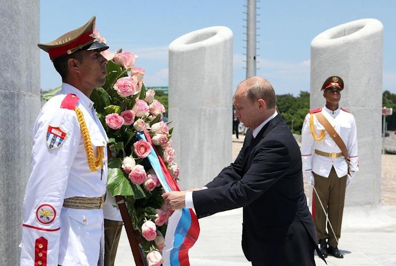 Russian President Vladimir Putin (R) participates in a wreath-laying ceremony at the Jose Marti monument in Revolution Square in Havana, on July 11, 2014 (AFP Photo/Alejandro Ernesto)