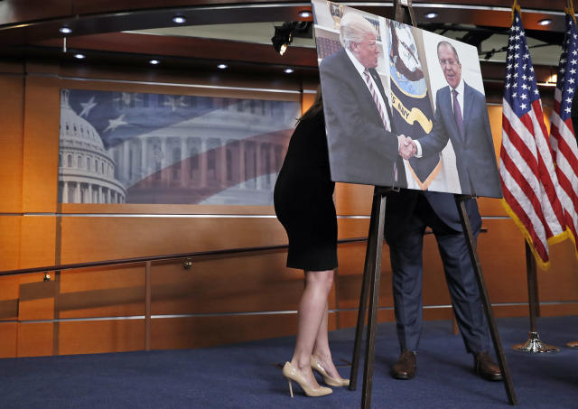 <p>An aide, left, speaks with Rep. Joe Crowley, D-N.Y., chairman of the House Democratic Caucus, and House Oversight and Government Reform Committee ranking member, on Capitol Hill in Washington, May 17, 2017, behind a photograph of President Donald Trump and Russian Foreign Minister Sergey Lavrov, during a news conference. (Photo: Alex Brandon/AP) </p>