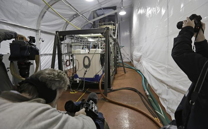 FILE - In this Thursday, Jan. 2, 2014, file photo, members of the media photograph one of two field deployable hydrolysis systems in a protective enclosure aboard the MV Cape Ray in Portsmouth, Va. The American ship MV Cape Ray is set to arrive Thursday, Feb. 13, 2014, at the naval base of Rota on Spain's southwestern coast used by the U.S. to resupply ahead of an unprecedented mission to collect and destroy mustard gas, raw materials for sarin nerve gas and tons of other highly toxic chemicals that form part of Syria's chemical weapons program. (AP Photo/Steve Helber, File)