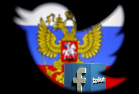 A Russian flag and a 3D model of the Facebook logo is seen through a cutout of the Twitter logo in this photo illustration taken in Zenica