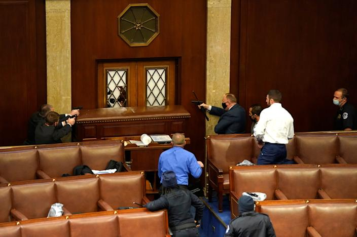 Law enforcement officers point their guns at a door that was vandalized in the House Chamber during a joint session of Congress.