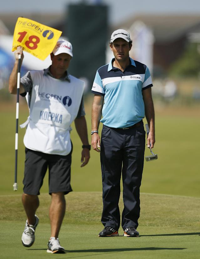 Edoardo Molinari of Italy waits to putt on the 18th green as Richard Elliot, the caddie of Brooks Koepka of the US, holds the flag during the first day of the British Open Golf championship at the Royal Liverpool golf club, Hoylake, England, Thursday July 17, 2014. (AP Photo/Alastair Grant)