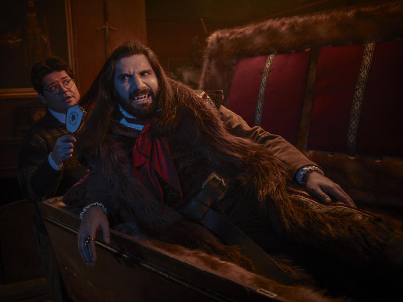 """This image released by FX shows Kayvan Novak and Harvey Guillen, left, in a scene from """"What We Do In the Shadows."""" The series premiering Wednesday is based on the 2014 cult-hit movie from New Zealand. (Matthias Clamer/FX via AP)"""