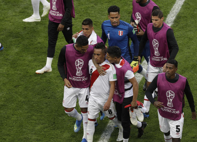 <p>Distraught: Cristian Cueva is consoled by his teammates as he leaves the field after Peru's defeat. (AP) </p>
