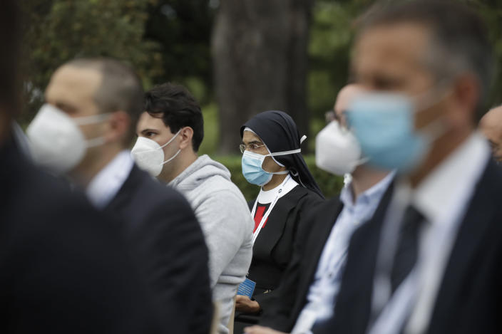 Faithful wearing face mask to prevent the spread of COVID-19 pray during a rosary lead by Pope Francis in Vatican gardens Saturday, May 30, 2020. Pope Francis is reciting a special prayer for the end of the coronavirus pandemic surrounded by a representative sampling of people on the front lines in his biggest post-lockdown gathering to date. (AP Photo/Alessandra Tarantino, pool)