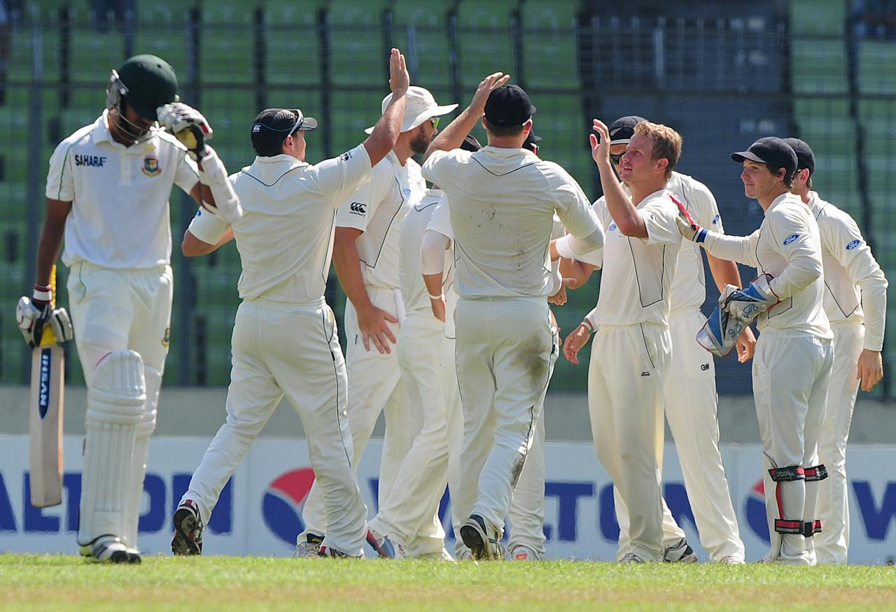 New Zealand cricketers congratulate teamate Neil Wagner (3rd R) after the dismissal of Bangladesh batsman Marshall Ayub (L) during the fourth day of the second cricket Test match between Bangladesh and New Zealand at the Sher-e Bangla National Stadium in Dhaka on October 24, 2013. AFP PHOTO/ Munir uz ZAMAN        (Photo credit should read MUNIR UZ ZAMAN/AFP/Getty Images)