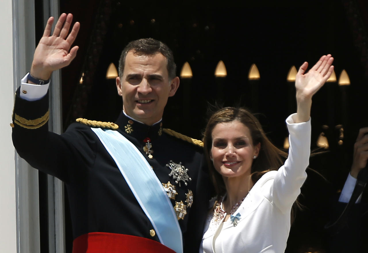 Spain's newly crowned King Felipe VI and his wife Spain's Queen Letizia wave to the crowd on a balcony of the Royal Palace in Madrid, Spain, on Thursday, June 19, 2014. Felipe is being formally proclaimed monarch Thursday after 76-year-old King Juan Carlos abdicated so that younger royal blood can rally a country beset by economic problems, including an unemployment rate of 25 percent. Felipe swore an oath at a ceremony with lawmakers in Parliament in front of Spain's 18th-century crown and 17th-century scepter. (AP Photo/Emilio Morenatti)