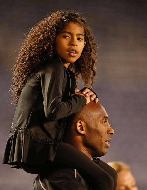 PHOTO: Gianna Maria-Onore Bryant sits on the shoulders of her father, Kobe, as they attend the women's soccer match between the United States and China Thursday, April 10, 2014, in San Diego. (Lenny Ignelzi/AP, File)