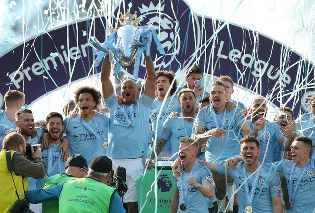 Foden celebrates with his team-mates as captain Manchester City captain Vincent Kompany lifts the Premier League trophy after victory at Brighton