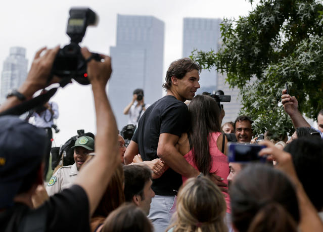 Rafael Nadal is mobbed by fans after posing for photographers with the U.S. Open tennis tournament men's singles championship trophy at Central Park, Tuesday, Sept. 10, 2013, in New York. Nadal defeated Novak Djokovic in four sets on Monday.(AP Photo/Julie Jacobson)