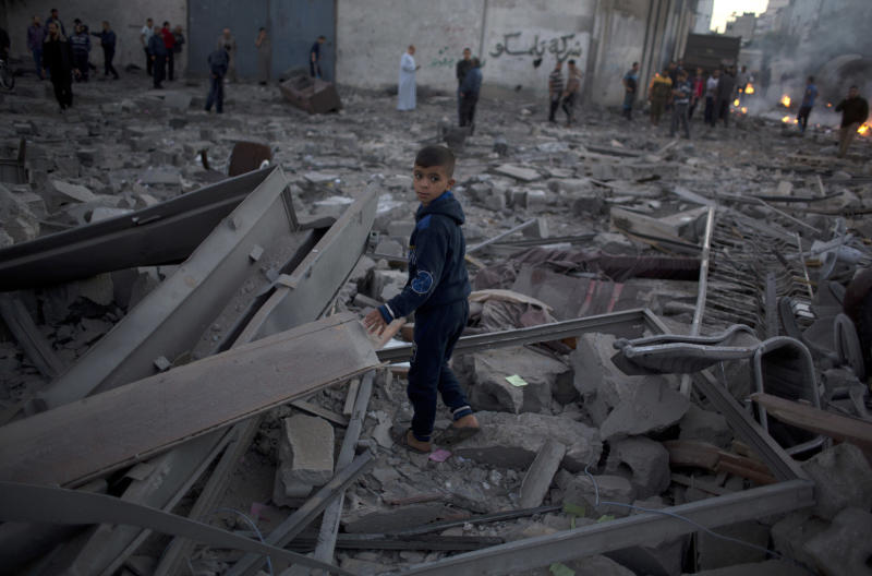 A Palestinian boy stands in the middle of the rubble of buildings destroyed by Israeli airstrikes early morning in Gaza City, Saturday, Oct. 27, 2018. Israeli aircraft have struck dozens of militant sites across the Gaza Strip as militants fired some 30 rockets into Israel. (AP Photo/Khalil Hamra)