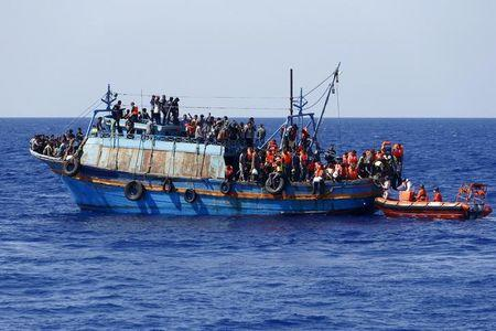FILE PHOTO - Migrants on board an overloaded wooden boat are rescued some 10.5 miles off the coast of Libya