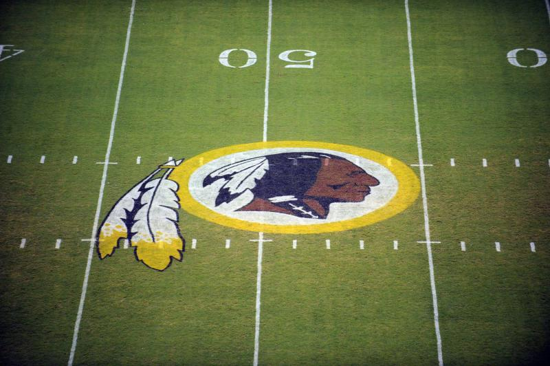 """<p> FILE - In this Aug. 28, 2009, file photo, the Washington Redskins logo is displayed at midfield before the start of a preseason NFL football game in Landover, Md. The team's nickname, which some consider a derogatory term for Native Americans, has faced a barrage of criticism. But a new Associated Press-GfK poll shows that nationally, """"Redskins"""" still enjoys widespread support. (AP Photo/Nick Wass, File)"""