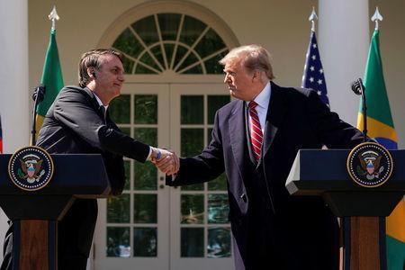 Brazil's President Jair Bolsonaro and U.S. President Donald Trump shake hands during a joint news conference in the Rose Garden of the White House in Washington, U.S., March 19, 2019. REUTERS/Kevin Lamarque