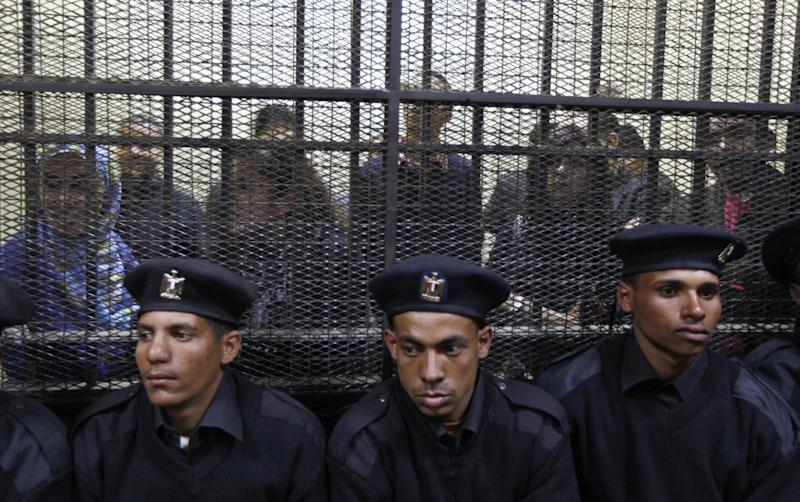 FILE - In this Sunday, Feb. 26, 2012 file photo, Egyptian policemen sit in front of Egyptian employees of several pro-democracy groups charged with using foreign funds to foment unrest during their trial in Cairo, Egypt. Egypt has lifted a travel ban on Wednesday, Feb. 29 for seven Americans charged with fomenting unrest by working for illegally funded pro-democracy groups, signaling an end to the worst crisis in Egypt-U.S. relations in 30 years. (AP Photo/Khalil Hamra, File)