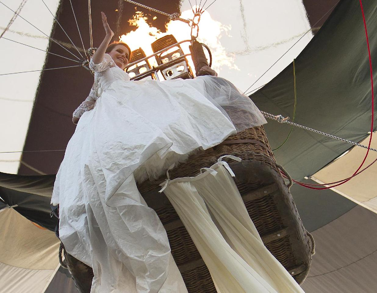Emma Dumitrescu, 17 years old, a model rides in a hot air balloon to show the worlds longest wedding dress train during a Guinness World Record attempt in Bucharest, Romania, Tuesday, March 20, 1012. Romania has set the world record for the world's longest bridal train.The nearly 3-kilometer (1.86-mile) long ivory train, which took 100 days to stitch, was showcased dramatically on Tuesday on the boulevard leading up to the giant palace built by late dictator Nicolae Ceausescu, seen in background. The previous record was 2.488 Km. (AP Photo/Vadim Ghirda)