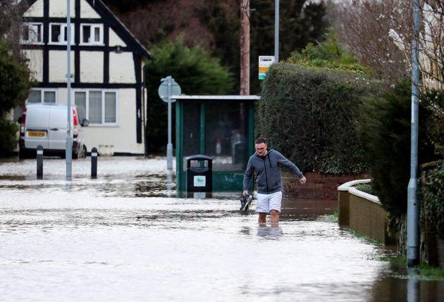 A man wades through flood water in Hereford.