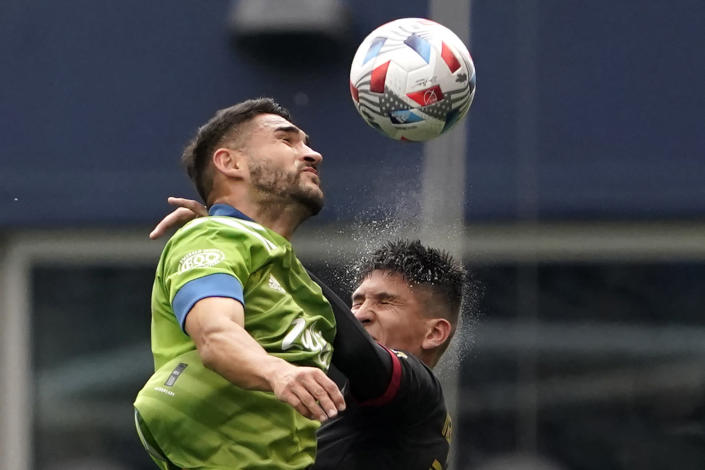 Seattle Sounders midfielder Cristian Roldan, left, heads the ball in front of Atlanta United midfielder Franco Ibarra, right, during the first half of an MLS soccer match, Sunday, May 23, 2021, in Seattle. (AP Photo/Ted S. Warren)