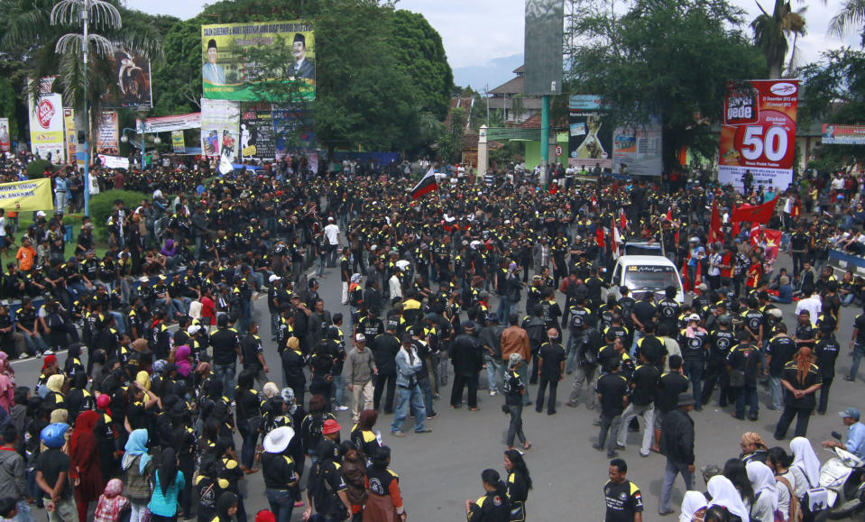 In this Friday, Dec. 21, 2012 photo, people crowd a main roundabout during a protest demanding District Chief Aceng Fikri to step down, in Garut, West Java, Indonesia. The Supreme Court late last month recommended that the president dismiss Fikri for violating the marriage law, following a public outrage after he divorced his second teenage wife by text message just four days after their wedding. The response has been seen as a small step forward for women's rights in the secular country where most people practice a moderate form of Islam. (AP Photo/Kusumadireza)