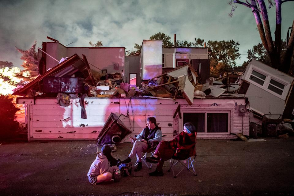 Bridget Casey sits in the driveway of her severely damaged home with her son Nate, 16, and daughter Marion, 14 (AP)