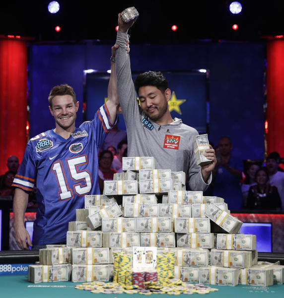 Tony Miles, left, holds up the arm of first place finisher John Cynn after the World Series of Poker main event, Sunday, July 15, 2018, in Las Vegas. (AP Photo/John Locher)