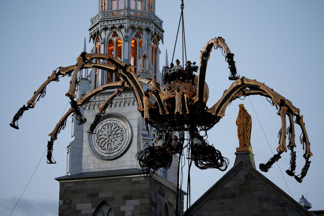 The giant mechanical spider Kumo, created by French production company La Machine, is lowered in front of the Notre-Dame Cathedral Basilica during a performance in Ottawa, Ontario, Canada, July 27, 2017. REUTERS/Chris Wattie     TPX IMAGES OF THE DAY