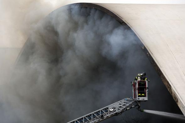 A firefighter watches from a cherry picker as water is sprayed into the Simon Bolivar Auditorium at the Latin America Memorial in Sao Paulo, Brazil, Friday, Nov. 29, 2013. The fire department of Brazil's biggest city says a fire swept through the large auditorium that is part of the political, cultural and leisure complex designed by famed architect Oscar Niemeyer. No casualties were reported. Two firefighters had to be treated for smoke inhalation. (AP Photo/Andre Penner)