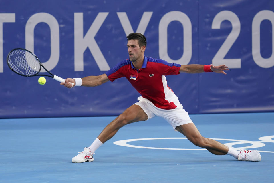 """FILE - In this July 28, 2021, file photo, Novak Djokovic, of Serbia, returns to Alejandro Davidovich Fokina, of Spain, during the third round of men's tennis at the 2020 Summer Olympics in Tokyo. If Djokovic wins the U.S. Open to complete the first calendar-year Grand Slam in men's tennis in 52 years, """"Rocket"""" Rod Laver will be there to welcome him into a remarkably exclusive club. (AP Photo/Patrick Semansky, File)"""