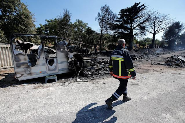 <p>A fireman walks past charred debris of vehicles that were destroyed by fire in a parking lot for camping cars in Bormes-les-Mimosas, in the Var department, France, July 26, 2017, after firefighters evacuated thousands of campers and local residents when a wildfire broke out on France's tourist-thronged Riviera coast overnight. (Jean-Paul Pelissier/Reuters) </p>