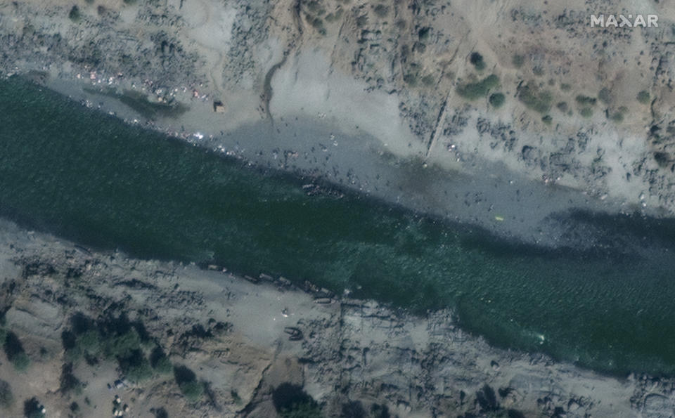 "This satellite image taken Sunday, Nov. 22, 2020 and released by Maxar Technologies, shows Ethiopian refugees gathered on the banks of the Tekeze River on the Sudan-Ethiopia border, near Hamdayet, eastern Sudan. Ethiopia's prime minister is rejecting growing international consensus for dialogue and a halt to deadly fighting in the Tigray region as ""unwelcome,"" saying his country will handle the conflict on its own as a 72-hour surrender ultimatum runs out on Wednesday. (Maxar Technologies via AP)"