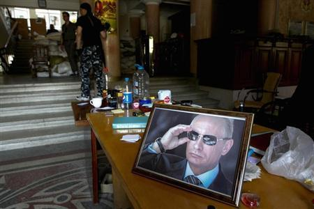 A portrait of Putin displayed on table in hall of state regional administration building occupied by pro-Russian activists in Luhansk