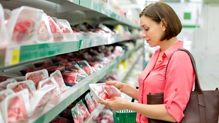 Woman buying meat in a supermarket