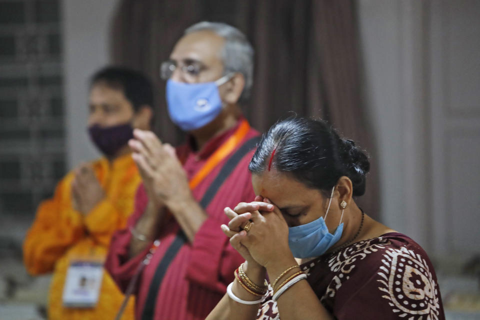 Members of the festival organizing team at the Kali Bari Hindu temple pray via live transmission on the first day of Durga Puja celebrations in New Delhi, India, Thursday, Oct. 22, 2020. Most of the festival festivities are being scaled down following the health officials warning about the potential for the coronavirus to spread during the religious festival season, which is marked by huge gatherings in temples and shopping districts. (AP Photo/Manish Swarup)