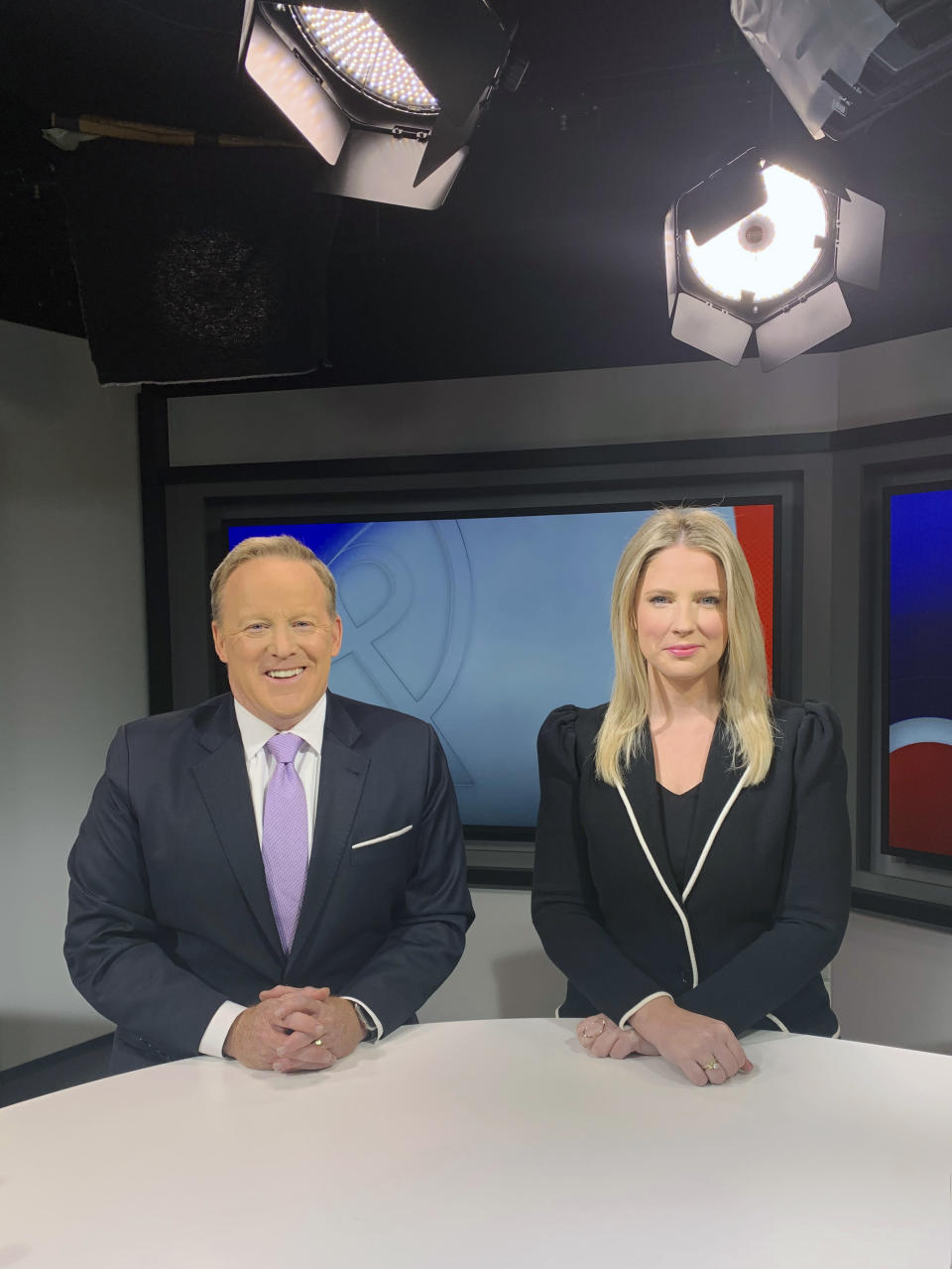 """In this image released by Newsmax, co-hosts Sean Spicer and Lyndsay Keith pose for a photo on the set of """"Spicer & Co."""" The network's rise in popularity has been astonishingly swift and could indicate the first serious threat to Fox News Channel's iron grip on conservative viewers in two decades. (Newsmax via AP)"""