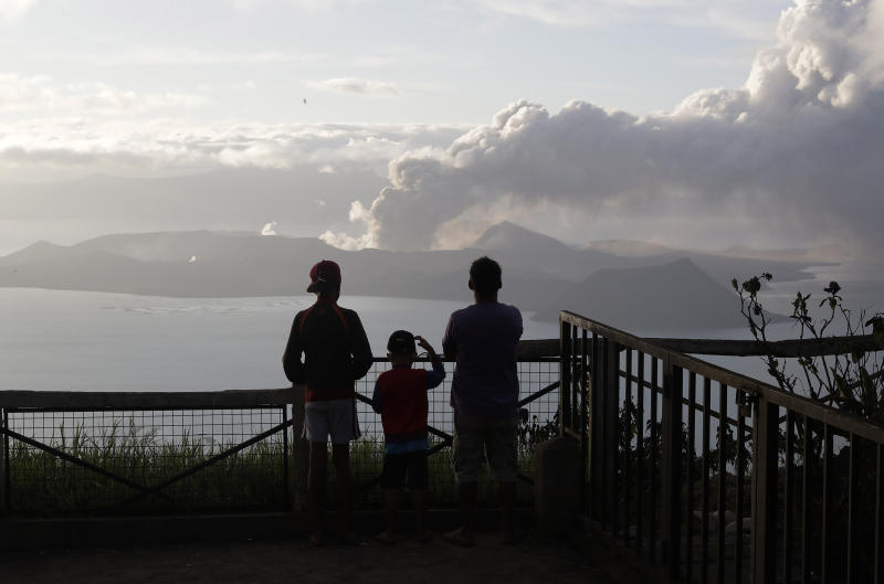 In this Tuesday, Jan. 14, 2020, photo, People watch from Tagaytay, Cavite province, south of Manila, as Taal Volcano continues to spew ash. Thousands of people fled the area through heavy ash as experts warned that the eruption could get worse and plans were being made to evacuate more.(AP Photo/Aaron Favila)
