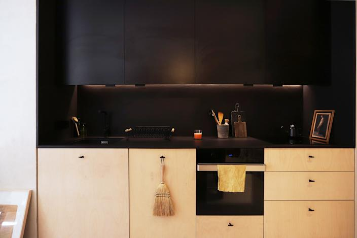 "<div class=""caption""> The sleek kitchen stands in dark contrast to the rest of the apartment. ""Armando loves to cook when we throw dinner parties,"" Natalia notes. </div>"
