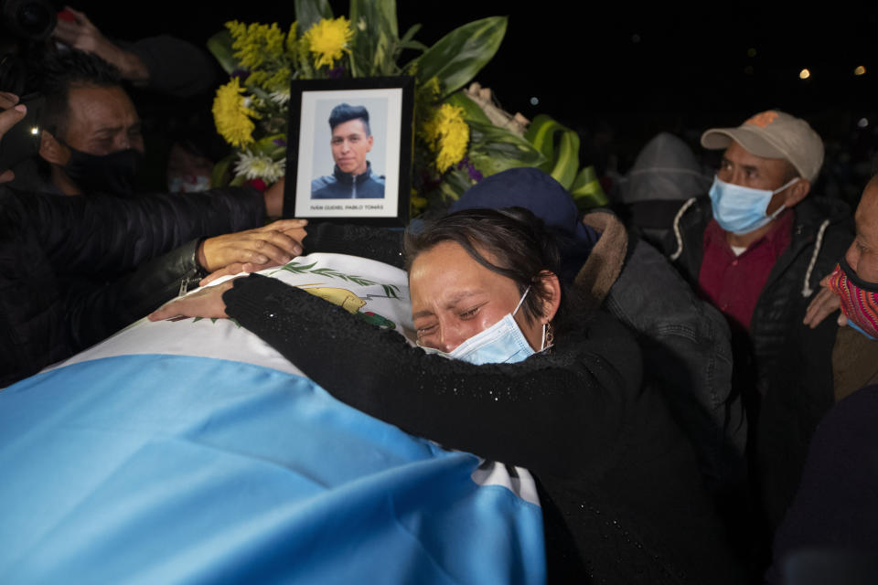 A relative grieves over the coffin containing the remains of Ivan Pablo Tomas, one of the Guatemalan migrants who was killed near the U.S.-Mexico border in January, at a memorial Mass in a soccer stadium in Comitancillo, Guatemala, Friday, March 12, 2021. The migrants were among 19 people shot and burned in Camargo, located in the northern Mexican state of Tamaulipas on Jan. 22. (AP Photo/Moises Castillo)