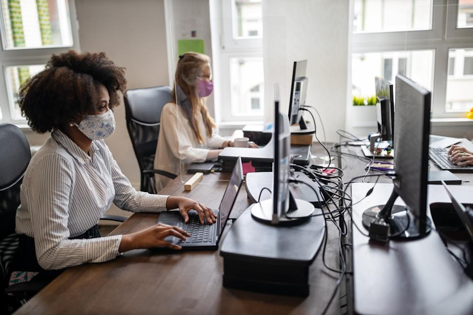 Some employees may continue having to wear masks at work. Image: Getty