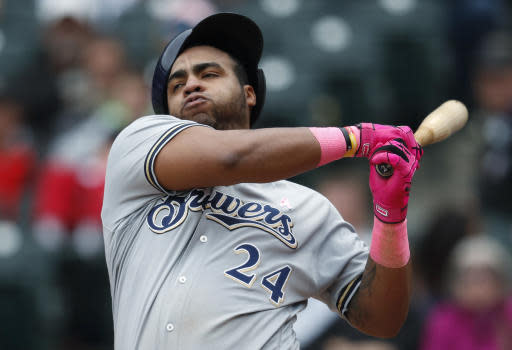 FILE - In this Sunday, May 13, 2018, file photo, Milwaukee Brewers' Jesus Aguilar almost loses his batting helmet while swinging at a pitch from Colorado Rockies relief pitcher Brooks Pounders in the eighth inning of a baseball game in Denver. Baseball is trying to resist, but it is being pulled into an era run by information overload and an all-or-nothing attitude. Today, hitters are concerned about launch angle, swing speed and exit velocity, according to Mike Schmidt. (AP Photo/David Zalubowski, File)