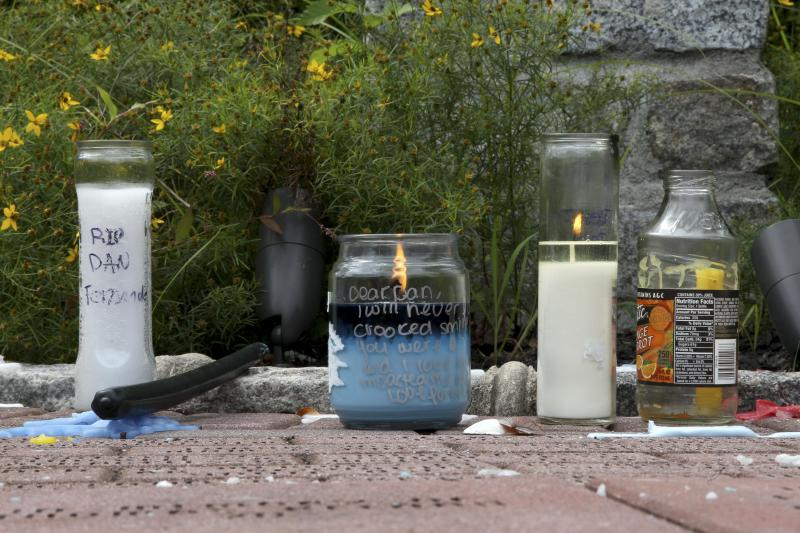 Remains of an informal memorial service for Daniel Fernandez, 16, are seen in front of St. Francis Preparatory School in New York, Sunday, Sept. 2, 2012. Fernandez, a teenager headed to a Sweet 16 party, was killed after he stuck his head out of the emergency hatch of a double-decker bus and hit the underside of a highway overpass, authorities said. (AP Photo/Seth Wenig)