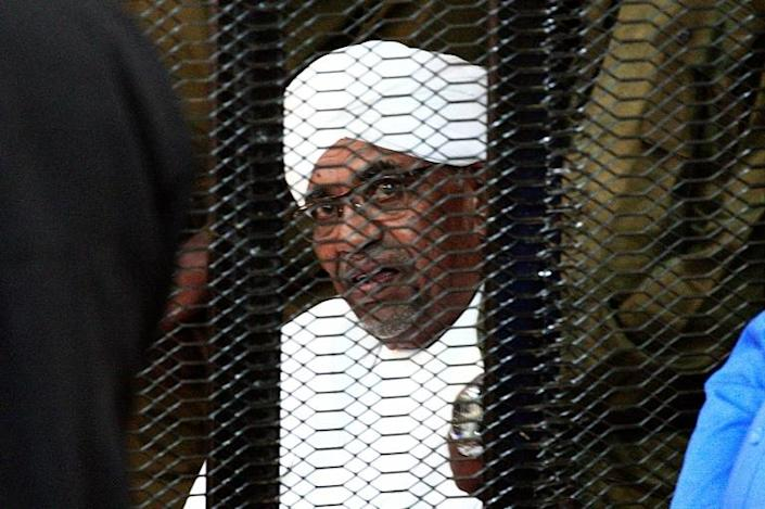 Sudan's deposed president Omar al-Bashir looks on from a defendant's cage during the opening of his corruption trial in Khartoum on August 19, 2019