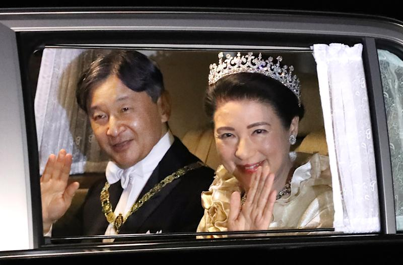Japan's Emperor Naruhito (L) and Empress Masako (R) arrive at the Imperial Palace to attend the court banquet in Tokyo on October 22, 2019. - Japan's new Emperor Naruhito completed his ascension to the ancient Chrysanthemum throne in a solemn, ritual-bound ceremony performed before hundreds of dignitaries in the Imperial Palace. (Photo by STR / JIJI PRESS / AFP) / Japan OUT (Photo by STR/JIJI PRESS/AFP via Getty Images)